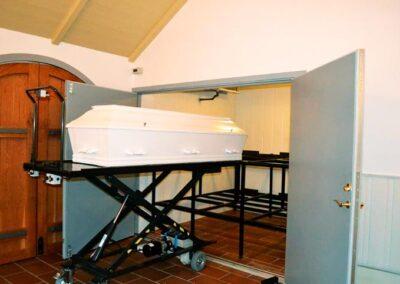 katafalk med hvid kiste og kistereol i kapel