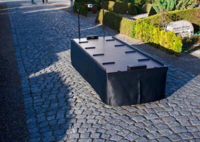 katafalk på kirkegaard med sort klæde